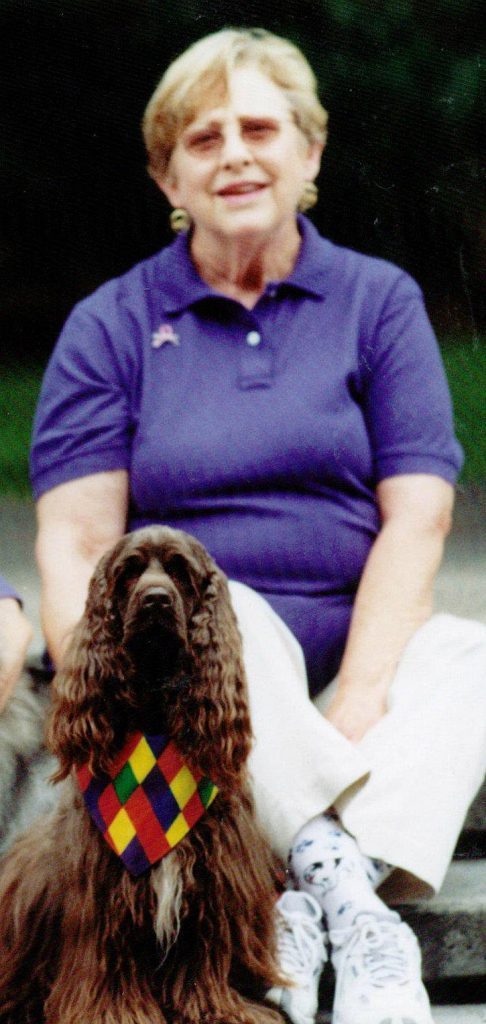Co-founder Carolyn Lenzi sits on steps outside. In front of her is her brown cocker spaniel, Bailey. Bailey was one of LAPS first therapy dogs.